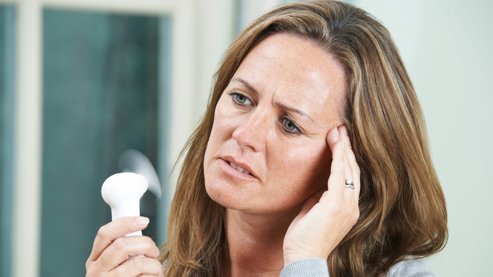 mulher com ventilador portátil para amenizar os sintomas da menopausa