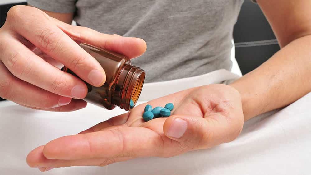 Close nas mãos de homem branco, uma virando um frasco com comprimidos azuis na palma da outra.
