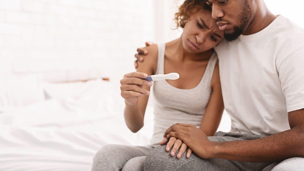 casal sentado na cama, olhando teste de gravidez negativo. Infertilidade atinge dez porcento dos casais