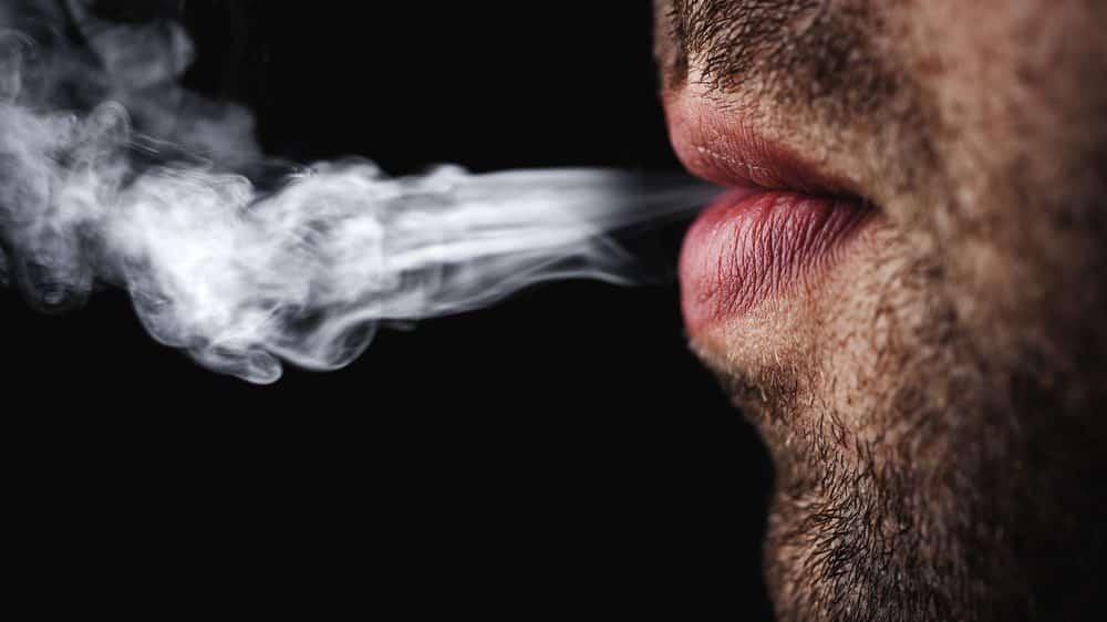 close de boca de homem soltando fumaça de cigarro