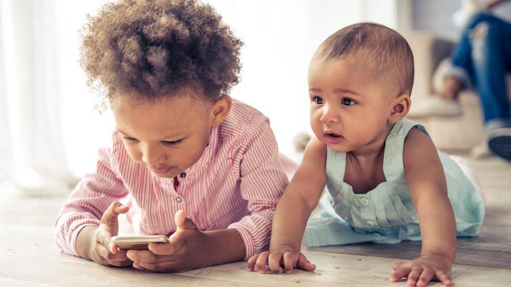 meninas pequenas brincam no chão com celular. Problemas de fala dificultam reconhecimento de vozes