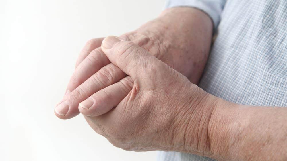 close em mão de idoso com dor nas articulações devido à osteoartrite