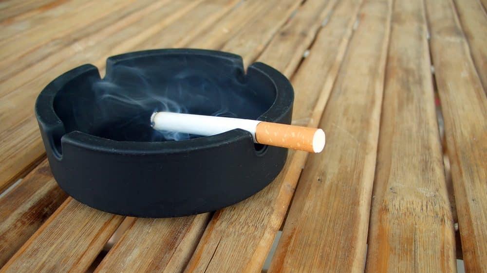 cigarro queimando em cinzeiro. dependência do cigarro é pior que de outras drogas