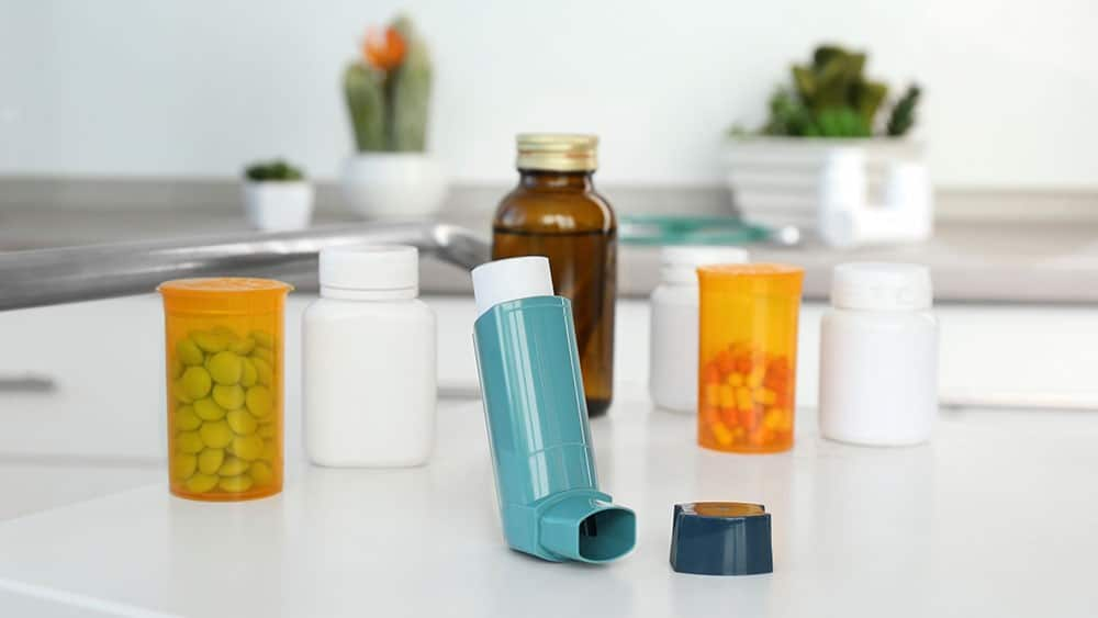 Bombinha de asma e potes de comprimidos sobre uma mesa.