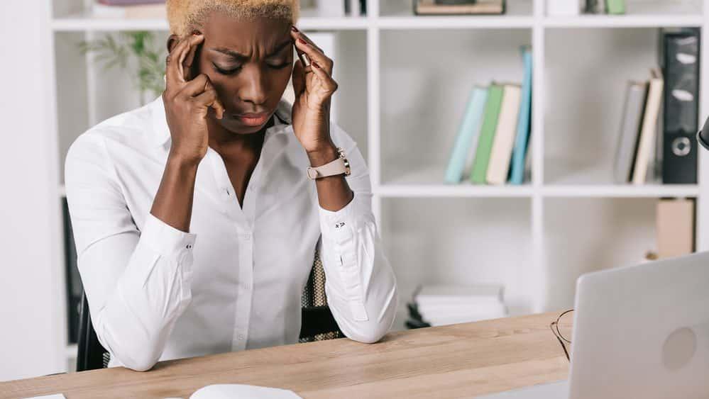 mulher com mãos nas têmporas e olhos fechados, em sinal de estresse, diante da mesa de trabalho