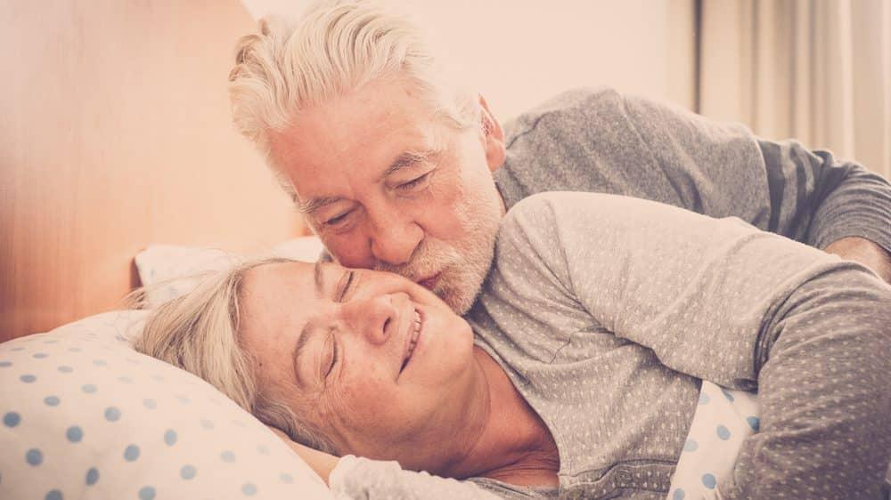 casal idoso se beijando na cama. há relação entre infarto e sexo