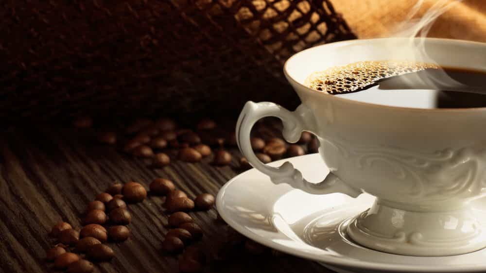 xícara de café com grãos ao lado. café e diminuição da mortalidade têm relação
