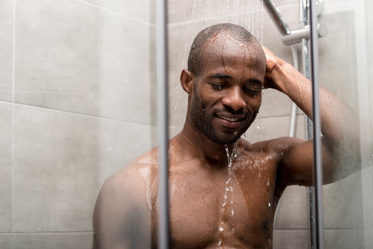 homem no chuveiro, cuidando da higiene íntima masculina
