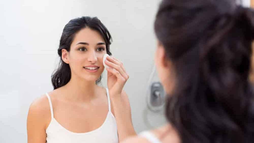 menina limpa o rosto para evitar acnes em frente ao espelho