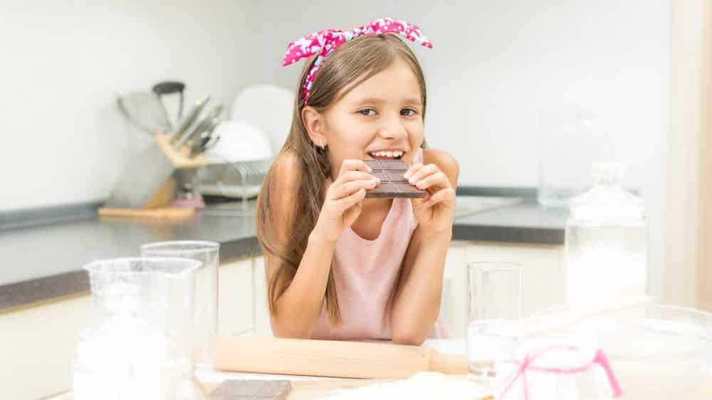 menina com dificuldade para engordar come chocolate