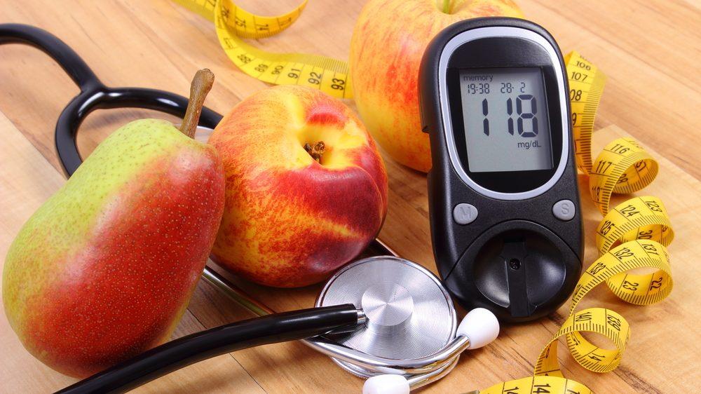 frutas, estetoscópio, fita métrica e aparelho de medir glicose para quem tem diabetes sobre uma mesa