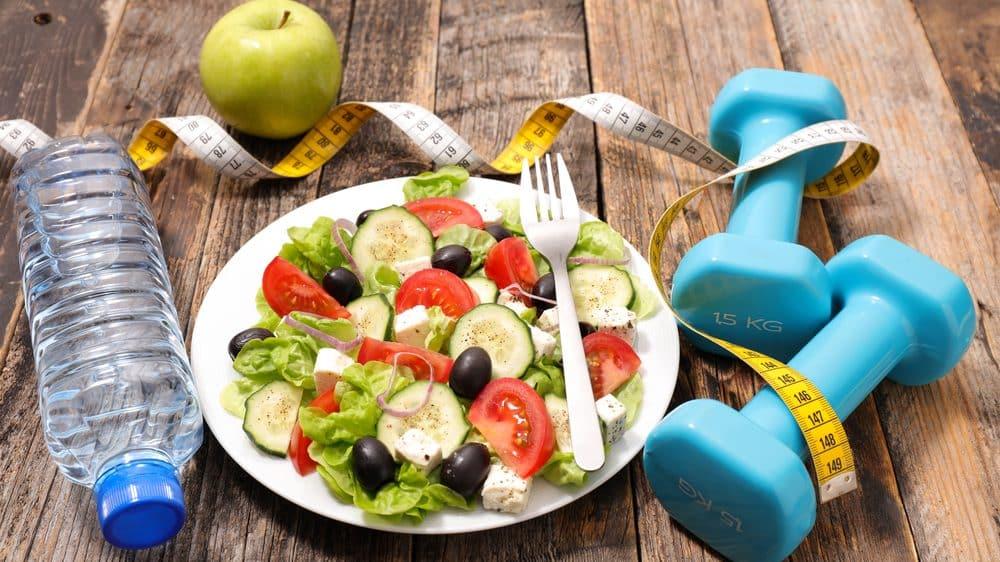 fruta, salada, fita métrica, garrafa de água e pesos sobre a mesa. veja mitos e verdades sobre obesidade