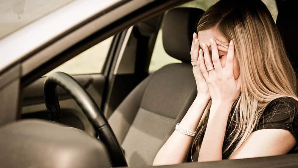 Mulher escondendo o rosto dentro de um carro.