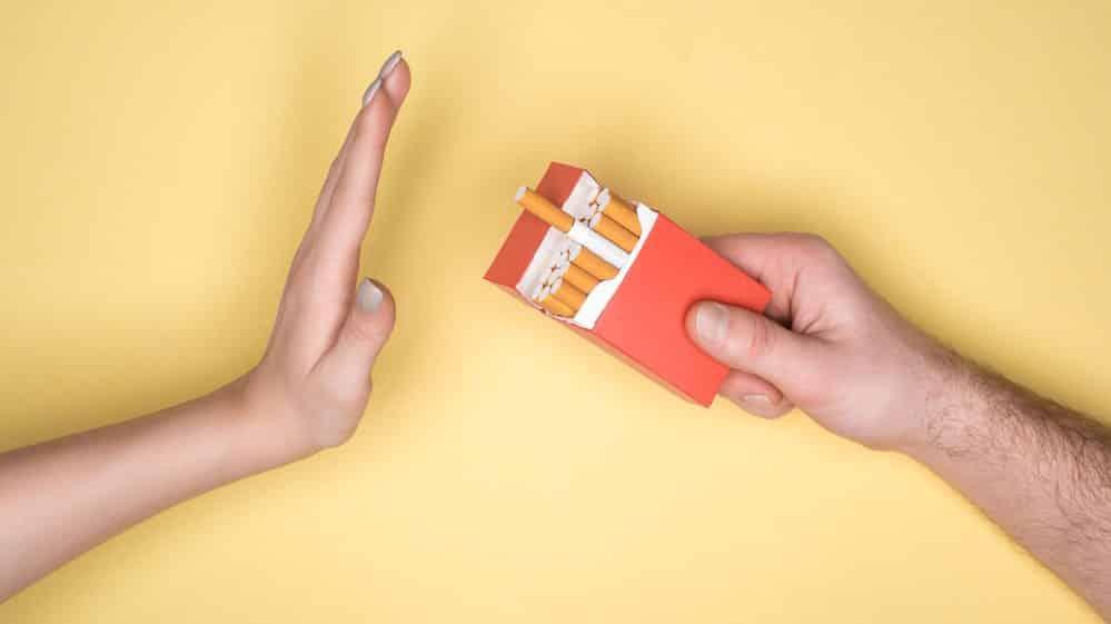 mão oferece maço de cigarro para outra mão, que recusa para parar de fumar