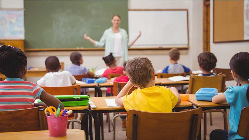 Sala de aula com crianças e uma no centro com a cabeça apoiada na mão, indicando desatenção.