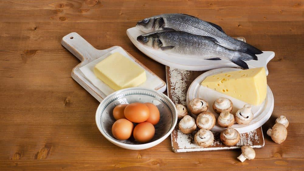 alimentos com vitamina D em mesa de madeira. ovos, peixe cru, manteiga e alho