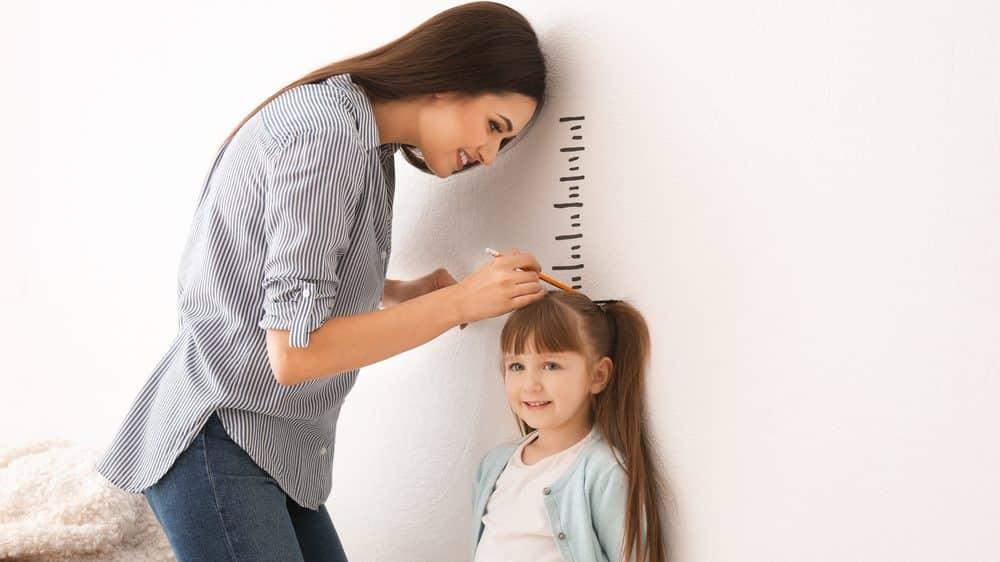 mãe mede filha encostada na parede. baixa estatura pode ter causas genéticas