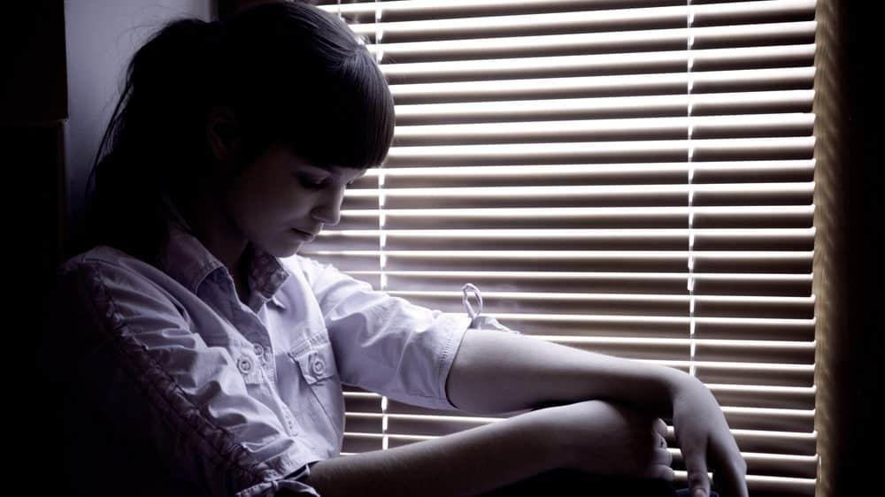 mulher deprimida sentada perto da janela. Transtorno bipolar aumenta risco de suicídio