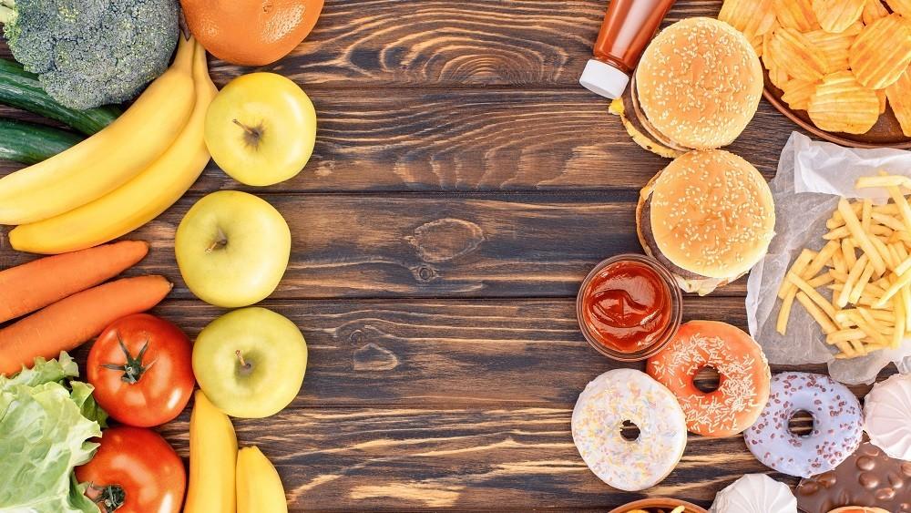 Alimentos saudáveis à esquerda da mesa e alimentos gordurosos à direita. Reduzir colesterol com medicamento deve ser último caso