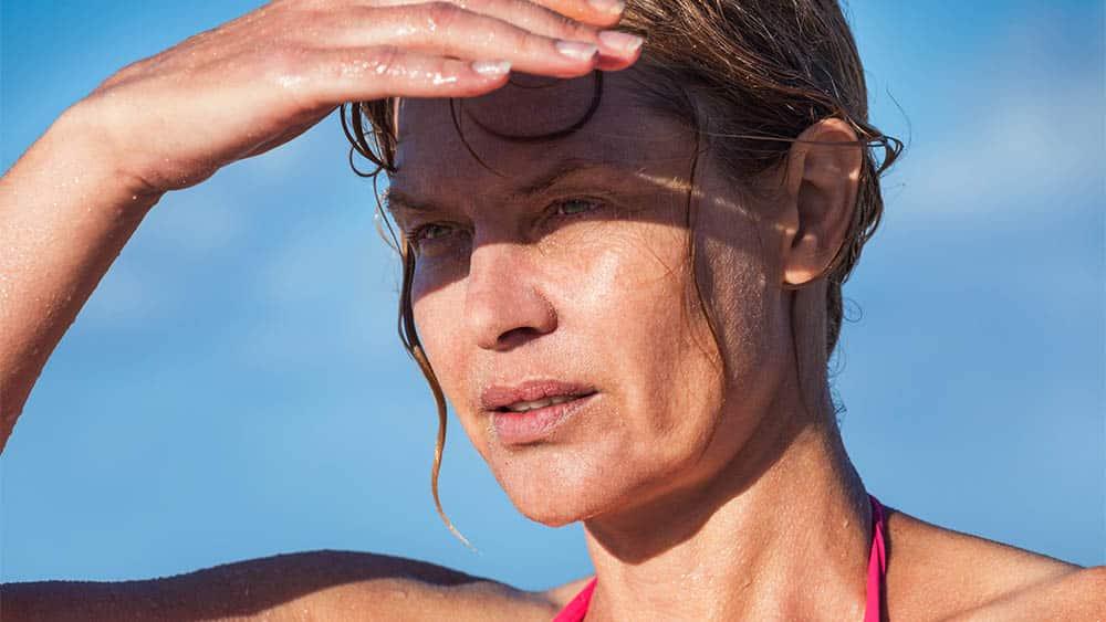 Mulher suada em dia quente protegendo os olhos com a mão.