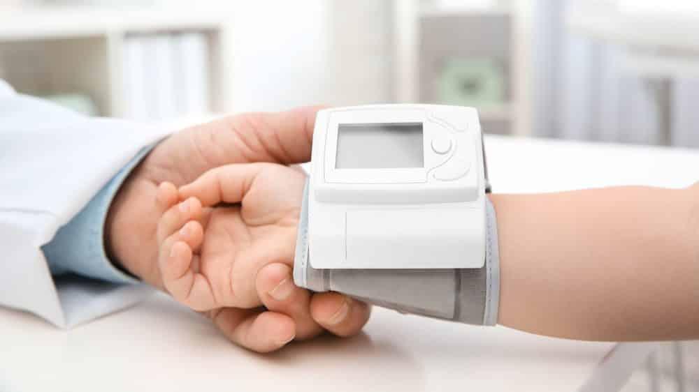 close de médico medindo o pulso de criança pequena com aparelho