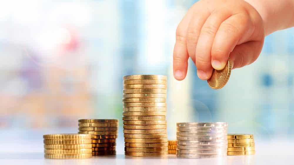 close de mão de bebê amontoando moedas. Pobreza e cognição estão relacionadas