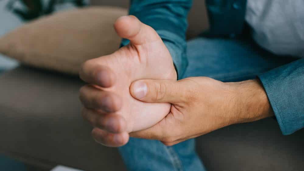 close de punho de homem com dor articular causada pela febre chikungunya