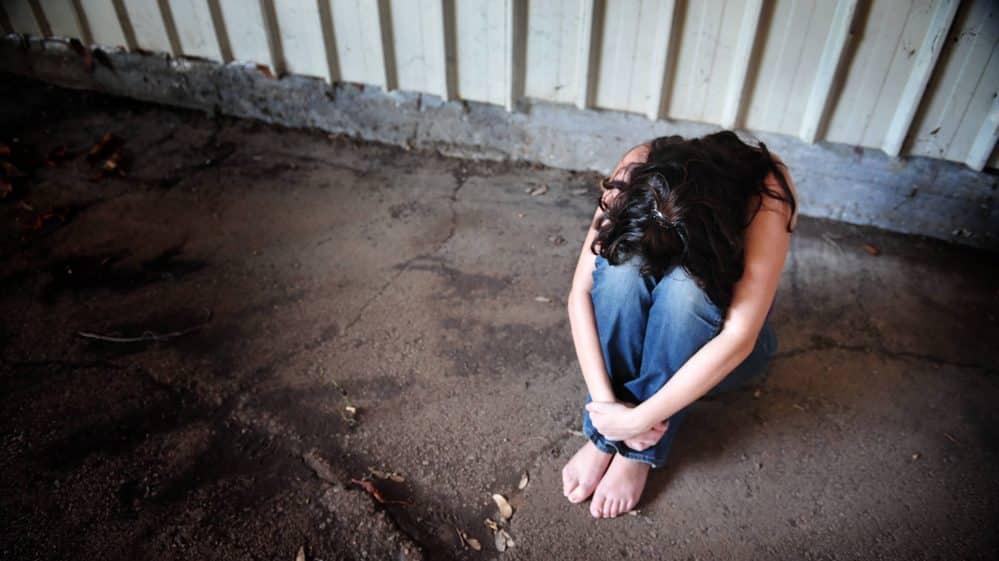 mulher com a cabeça entre os joelhos. violência universitária deve ser enfrentada