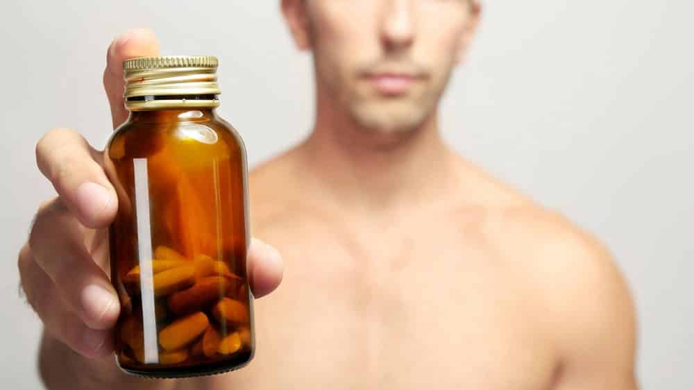 homem segurando frasco de remédio. indicação de reposição de testosterona é controversa