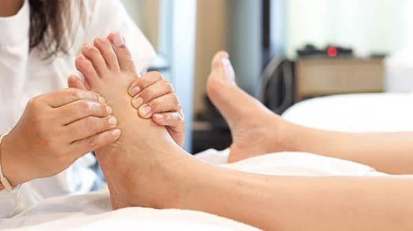 especialista massageando os pés de paciente