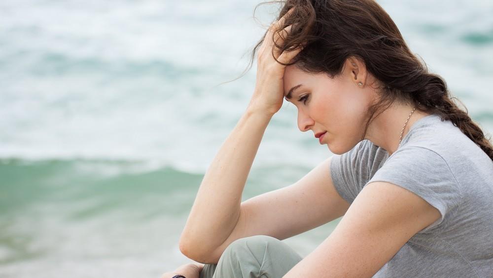 Mulher com a mão na cabeça, demonstrando preocupação e tristeza. veja as fases do luto