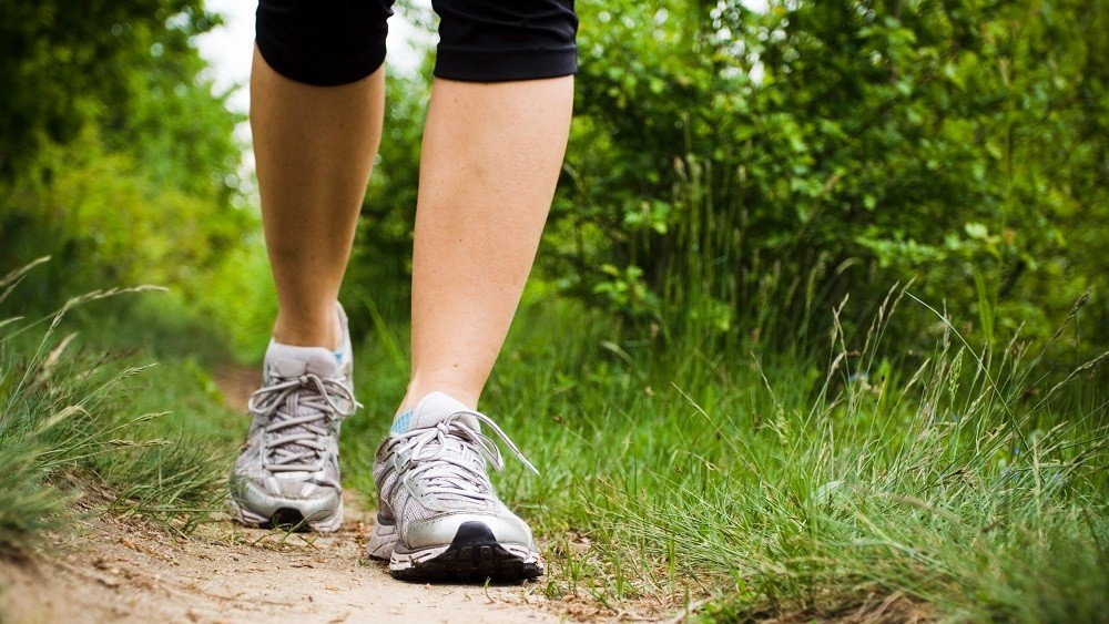Pernas de uma mulher caminhando ao ar livre.