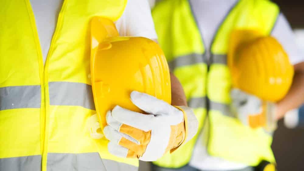 trabalhadores com trajes de segurança que garantem menos acidentes de trabalho
