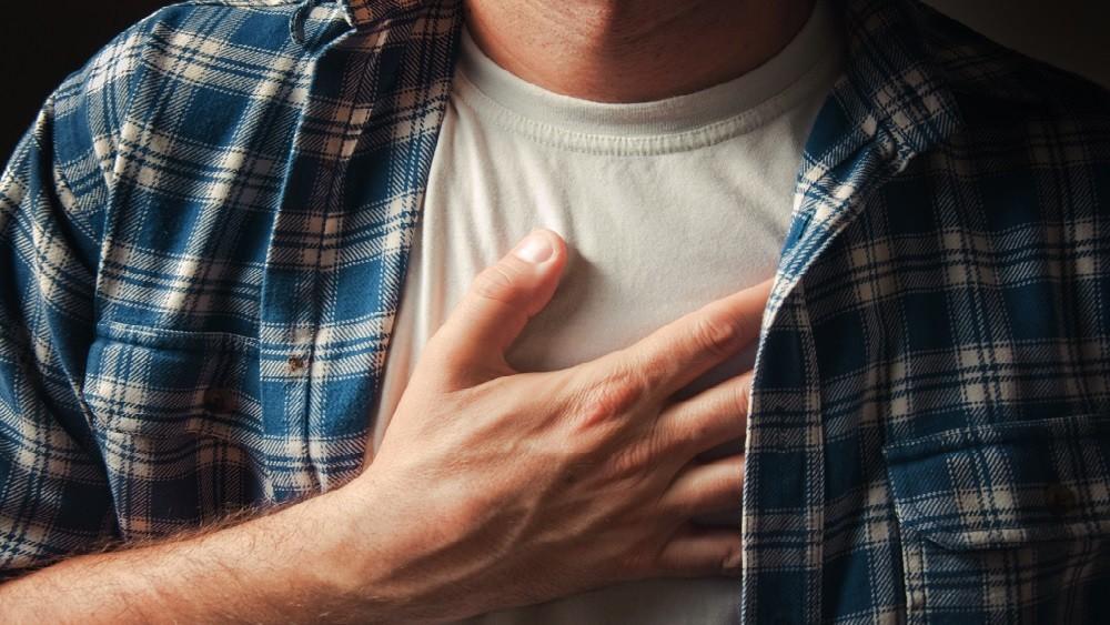 Homem com mão no peito, demonstrando dor.