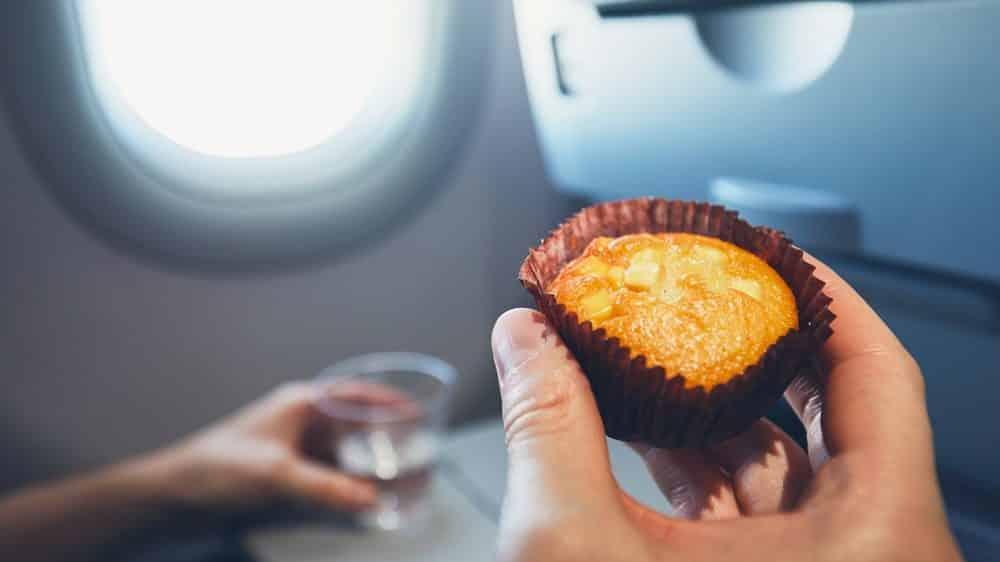 homem segura muffin em avião. excesso de peso é problema grave de saúde
