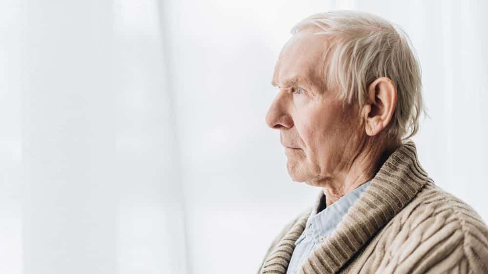 idoso com demência avançada sentado, olhando para a frente