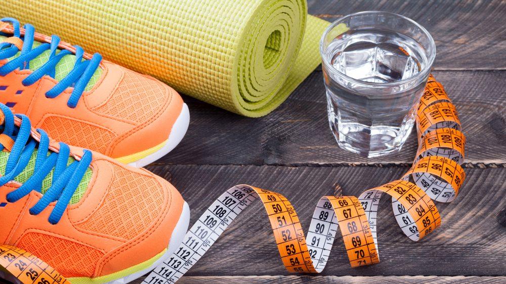 par de tênis, tapete de ioga, copo de água e fita métrica. Veja como lidar com a quarentena e produtividade