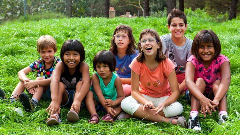 crianças de biotipos diferentes sentadas e rindo. Genética das raças não permite distinguir raça com base em traços