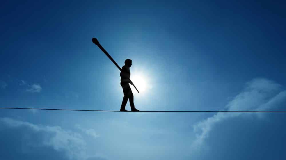 homem caminhando em corda ao ar livre. idiotice masculina é o risco maior que homens têm de cometer erros tolos
