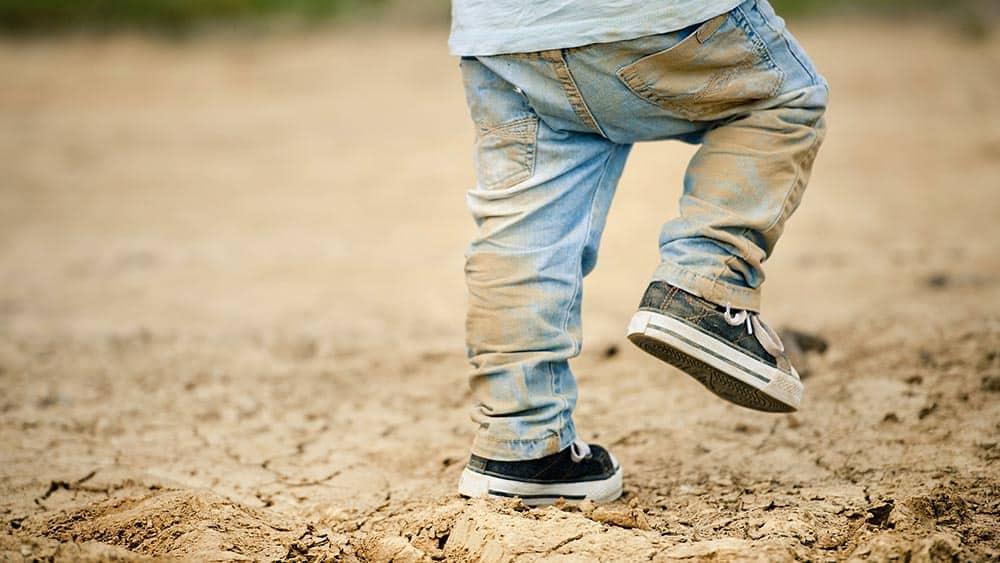 Menino brincando em chão de terra com jeans sujo. Relação entre germes e asma vem sendo estudada.