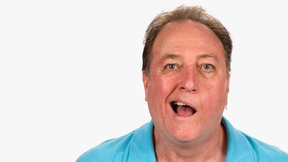 Homem abrindo a boca demonstrando a paralisia facial periférica atingindo a metade esquerda de seu rosto.