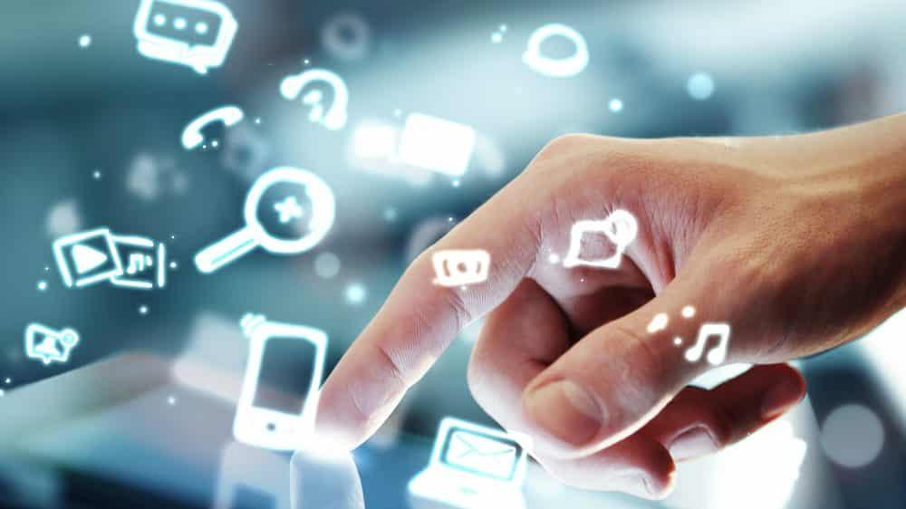 mão toca tablet e ícones de redes sociais saltam da tela. Internet divulga desinformação em excesso