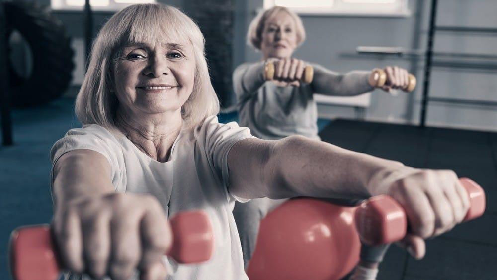 Duas senhoras levantando pesinhos na academia.