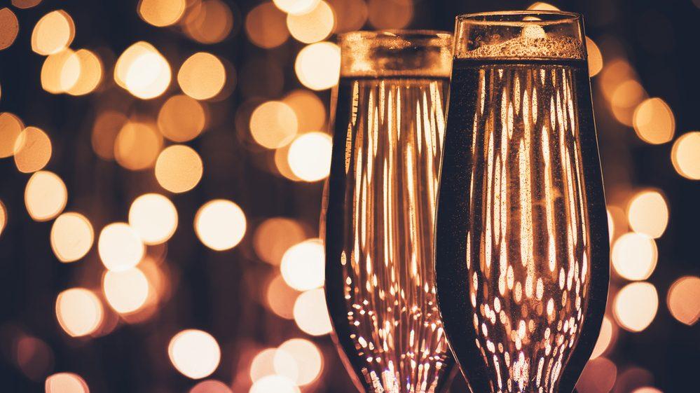 duas taças de champanhe com luzes ao fundo. o fim de ano é época que traz mais problemas que alegrias