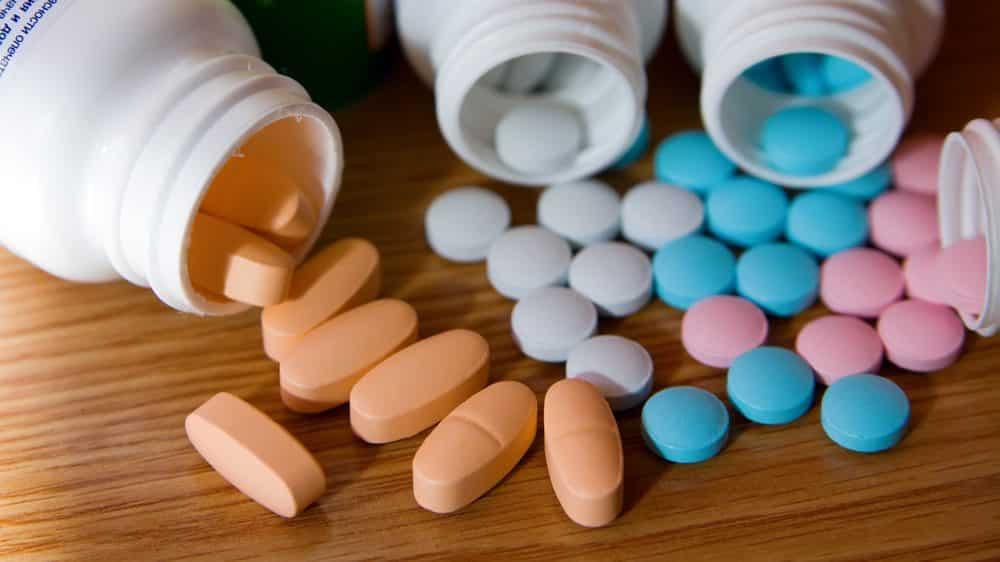 close em frascos de vitaminas abertos, com pílulas sobre a mesa. Suplementos nutricionais para câncer são desnecessários
