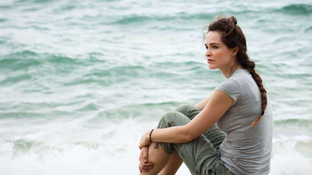 mulher pensativa sentada na beira do mar. O controle do corpo da mulher se dá por imposições sociais