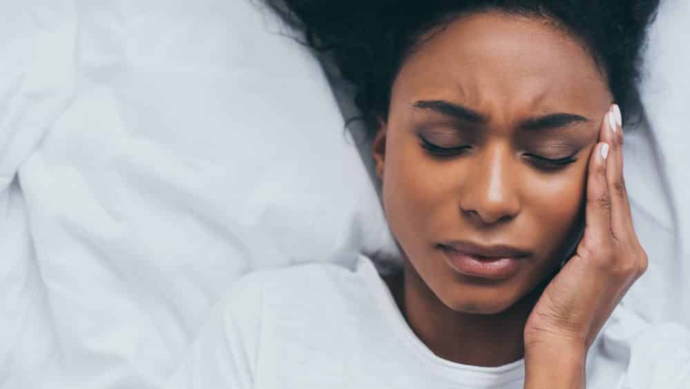 mulher deitada com mão na têmpora, em sinal de dor por causa de crises de enxaqueca