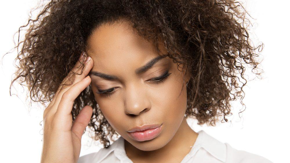 mulher apreensiva, com a mão na testa. Pancadas na cabeça podem estar associadas á demências