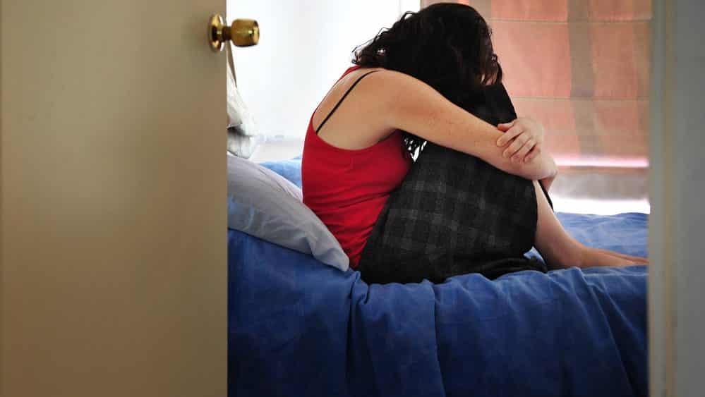 Mulher deprimida, encolhida em cima da cama. Estupro deixa sequelas físicas e psicológicas