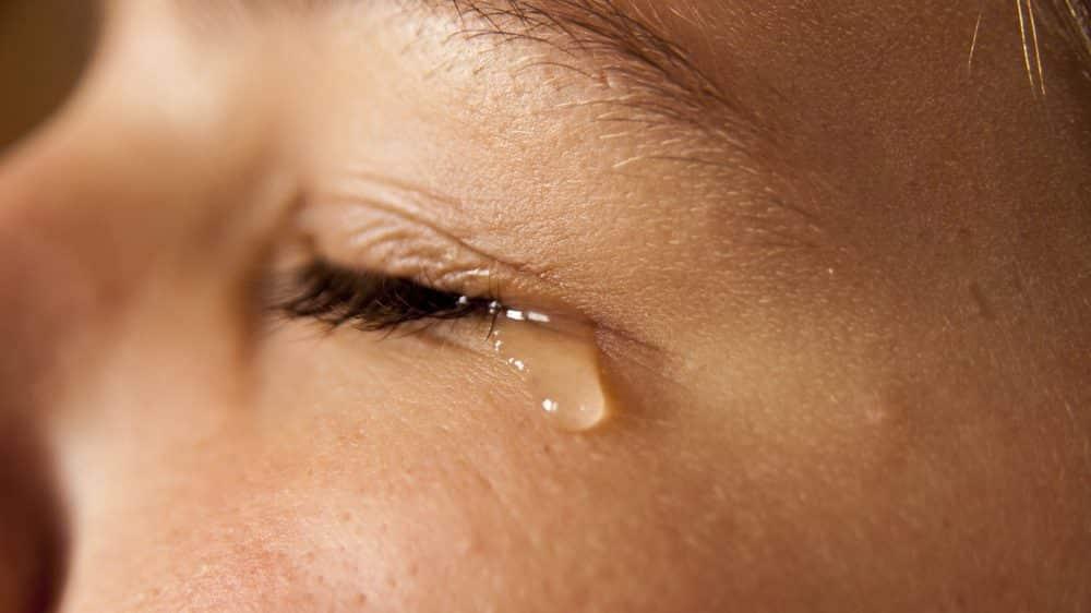 close em rosto de mulher chorando. A lágrima de choro tem composição diferente